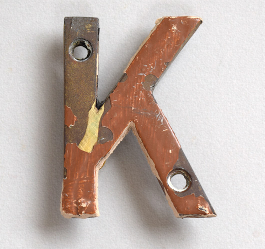 Small vintage brass sign letter 'K' painted brown, early 1900s