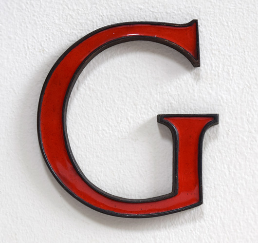 Small antique red enamel and brass letter 'G', c. 1910