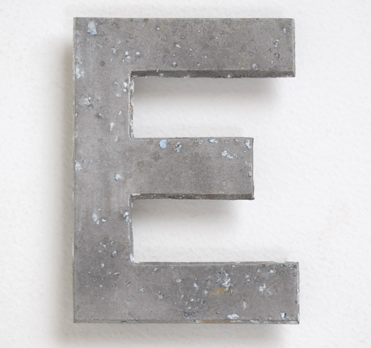 Early vintage cast-metal car number plate letter 'E'