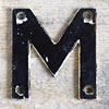 Mid-1900s monochrome metal sign letter 'M'