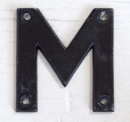 Mid-1900s vintage black painted metal sign letter 'M'
