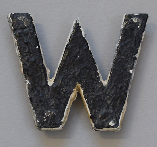 Early-1900s black & white metal sign letter: W