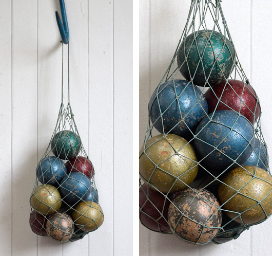 Early-1900s antique wooden game balls with net