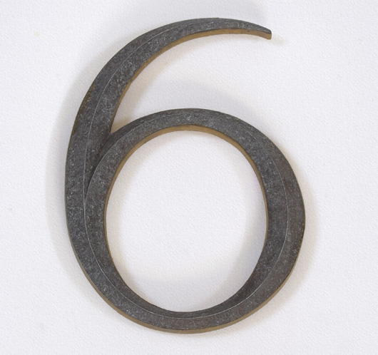 Vintage cast-metal and wood building number: '6' or '9'
