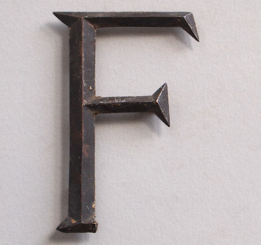 Early-1900s stylised vintage brass sign letter 'F', tarnished