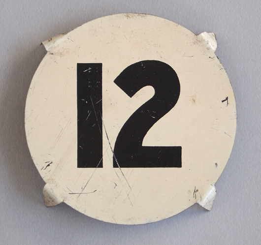 Early-1900s round vintage tin number marker: '12'