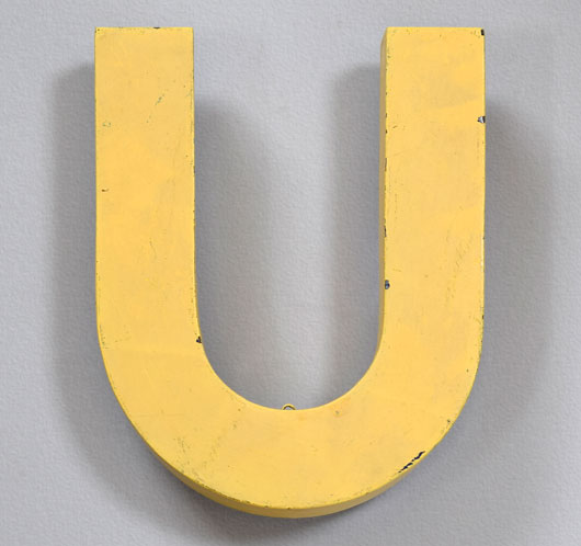 Vintage yellow painted metal shop sign letter 'U'