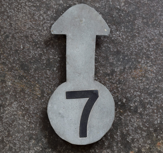 Vintage numbered zinc metal arrow pointer: '7'