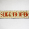 Painted tin sign: Slide To Open