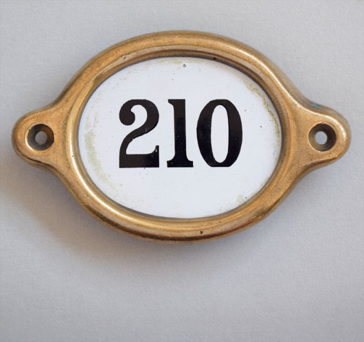 Early-1900s vintage brass and enamel hotel door number: '210'