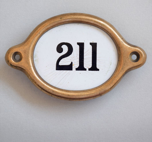 Early-1900s vintage brass and enamel hotel door number: '211'