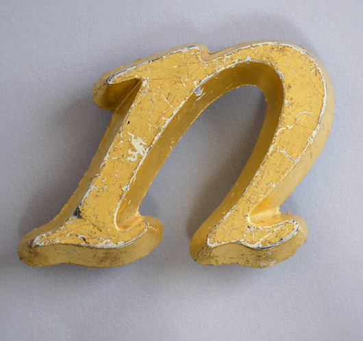 Vintage gold-leaf lowercase italic letter 'n' or 'u', early 1900s