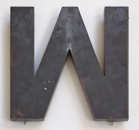 Large vintage charcoal-grey metal letter 'M' or 'W'